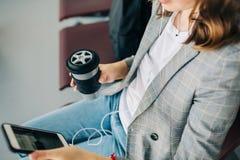 overview Menina que senta-se no aeroporto com smartphone foto de stock
