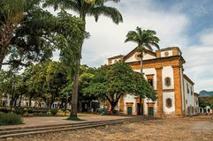 Overview of old colored church, garden with trees and cobblestone street in Paraty. Overview of old colored church, garden with trees and cobblestone street in stock photo