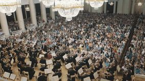Overview of old style concert hall during violin orchestra concert. Lot of people stock video