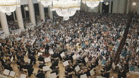 Overview of old style music hall during string orchestra concert. Lot of people stock footage