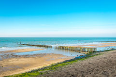 Overview of a part of the Dutch North Sea coast. Overview of the Dutch North Sea coast with a long asphalt-covered seawall. In the sea is a traditional Royalty Free Stock Images