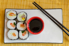 Overview of six sushi rolls with soy sauce and chopsticks. Six sushi rolls served on a rectangular plate with a bowl of soy sauce and chopsticks Royalty Free Stock Image