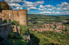 Overview of stone tower, green hills, vineyards and town rooftops near a road. From the city center of Orvieto. Overview of stone tower, green hills, vineyards Royalty Free Stock Photos