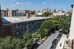 Overview of a street in Harlem, in New York City, USA. New York City, USA - July 28, 2018: Overview of a street with its old typical houses and people around in stock photography