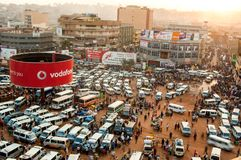 Overview of Taxi park, Kampala. Aerial view and overview of old taxi park, or mini-bus station, with public buildings and shopping malls behind, Kampala, Uganda Royalty Free Stock Image