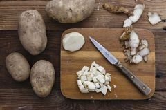 Cutting potatoes on a cutting board royalty free stock images