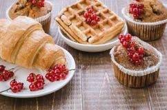 Overvloed van gebakjes die met rode aalbes worden verfraaid/overvloed van gebakjes die met rode aalbes op een houten achtergrond  stock afbeeldingen