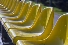 Overvloed van gele plastic zetels Lange reeks Stock Foto