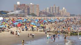 Overvol Coney Island-strand op een warme, wazige dag stock foto's
