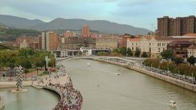 Overvol riverbank en boten die zich onderaan rivier, bergen en cityscape bij rug bewegen stock footage