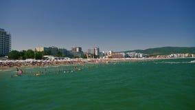 Overvol strand met mensen stock footage