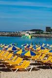 Overvol strand met zonparaplu's en stoelen die op toeristen, betaald de dienst op stranden wachten stock foto's