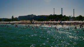 Overvol strandhoogtepunt van mensen sunbeds en paraplu's stock videobeelden