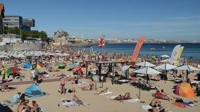 Overvol zandig strand in Cascais dichtbij Lissabon, Portugal tijdens de zomer Dit strand is genoemd geworden Praia DA Conceicao stock footage