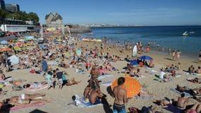 Overvol zandig strand in Cascais dichtbij Lissabon, Portugal tijdens de zomer Dit strand is genoemd geworden Praia DA Conceicao M stock videobeelden
