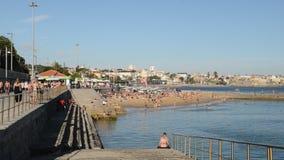 Overvol zandig strand in Cascais dichtbij Lissabon, Portugal tijdens de zomer Dit strand is genoemd geworden Praia das Moitas stock footage