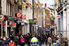 Overvolle het winkelen straat met vele mensen en winkelstekens op beroemde Nieuwendijk-straat in Amsterdam, Nederland Stock Fotografie