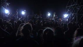Overvolle plaats met mensen die bij een rotsoverleg partying stock footage