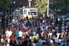 Overvolle straat met mensen en een tramauto stock foto's