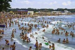 Overvolle strand en mensen in de overzeese golven stock afbeeldingen