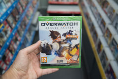 Overwatch videogame on XBOX One. Bratislava, Slovakia, circa april 2017: Man holding Overwatch videogame on Microsoft XBOX One console in store Royalty Free Stock Photos