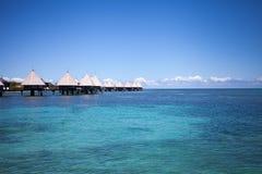 Overwater brunnsort och bungalower i den tropiska blåa lagun Arkivbilder