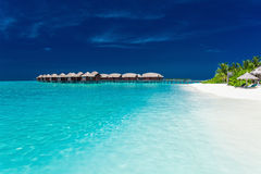 Overwater bungallows in blue lagoon on tropical island royalty free stock image
