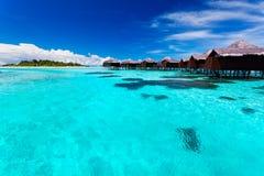 Overwater bungallows in der blauen tropischen Lagune Lizenzfreies Stockfoto