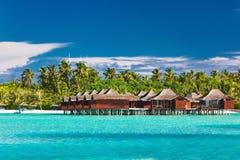 Overwater bungallows i lagun på den tropiska ön med kokosnöt p Arkivfoton