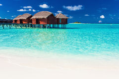 Overwater bungalow and beach in blue lagoon of tropical Maldives Stock Photo