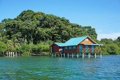 Overwater bungalow with lush tropical vegetation Royalty Free Stock Photography