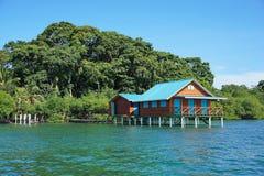 Overwater bungalow med frodig tropisk vegetation royaltyfri fotografi