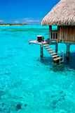 Overwater bungalow resort. Bungalow vacation resort with turquoise blue waters in tahiti Royalty Free Stock Images