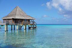 Overwater bungalow with thatched roof in lagoon Royalty Free Stock Photography