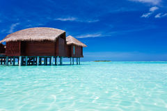 Overwater bungalow in tropical lagoon Royalty Free Stock Image