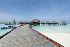 Overwater bungalows boardwalk in Maldives. Boat and overwater bungalows boardwalk of the Maldives royalty free stock images
