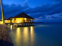 Overwater bungalows in tropical island. Maldives - at the sunset time stock images