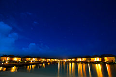 Overwater bungalows on the tropical island resort of Maldives at. Night with heaven full of stars stock photography