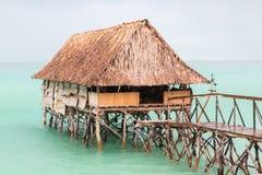 Overwater thatched roof bungalow hut of Micronesian people, lagoon of South Tarawa, heavy rain shower, wet season, Kiribati, royalty free stock photo