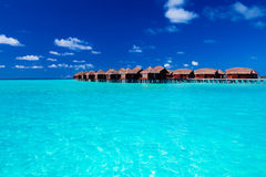 Overwater villas in blue tropical lagoon Royalty Free Stock Photography