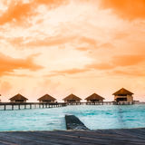 Overwater villas in blue tropical lagoon Stock Photo