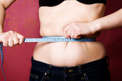 Overweight. Trying to fit in measurement standard. overweight problems Stock Photo