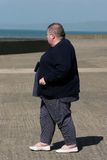 Overweight. Female walking alone on a beach promenade Royalty Free Stock Photography