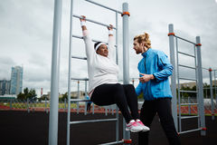 Overweight African woman practicing hanging double leg raise. Weight-loss practice with personal trainer stock image