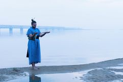 Overweight bearded man in blue kimono standing on river bank in fog looking at wooden stick royalty free stock images