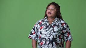 Overweight beautiful African woman against green background. Studio shot of overweight beautiful African woman against chroma key with green background stock footage