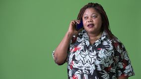 Overweight beautiful African woman against green background. Studio shot of overweight beautiful African woman against chroma key with green background stock video footage
