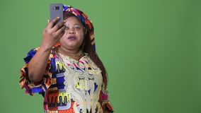 Overweight beautiful African woman wearing traditional clothing against green background. Studio shot of overweight beautiful African woman wearing traditional stock footage