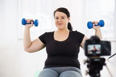Overweight blogger recording content for vlog. Fitness trainer, internet sporting class, training online video course. overweight blogger recording content for royalty free stock images