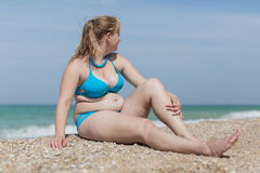Overweight blond at the sea. Adult plump woman in bikini sitting on pebble against the sea stock photo